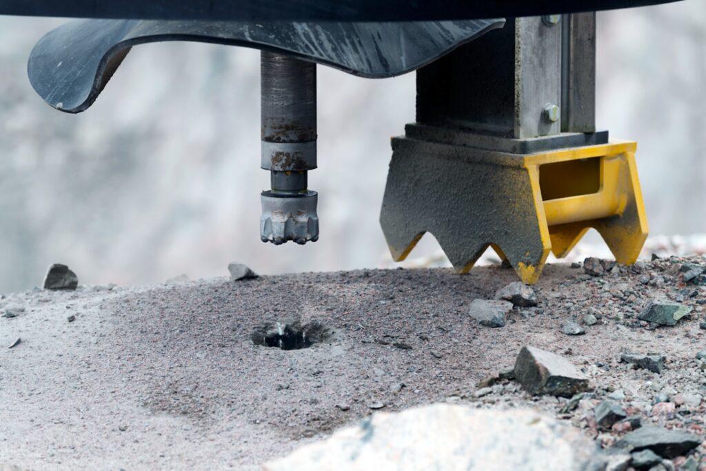 Närbild av en borrkrona på en borrigg som borrar ett hål i berget
