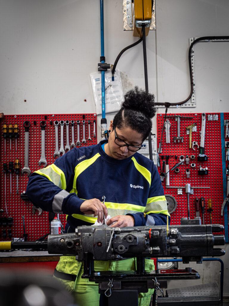 En ung kvinna jobbar med en bergborrmaskin i borrmaskinsverkstaden i Slagsta. Verktygen hänger på väggen bakom henne.