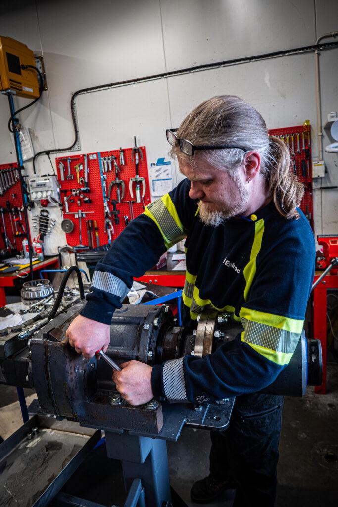 Mats Långdal skruvar i en bergborrmaskin i borrmaskinsverkstaden hos Epiroc.