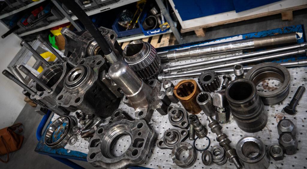 Delarna från en borrmaskin ligger uppradade på en arbetsbänk i Epirocs borrmaskinsverkstad i Slagsta