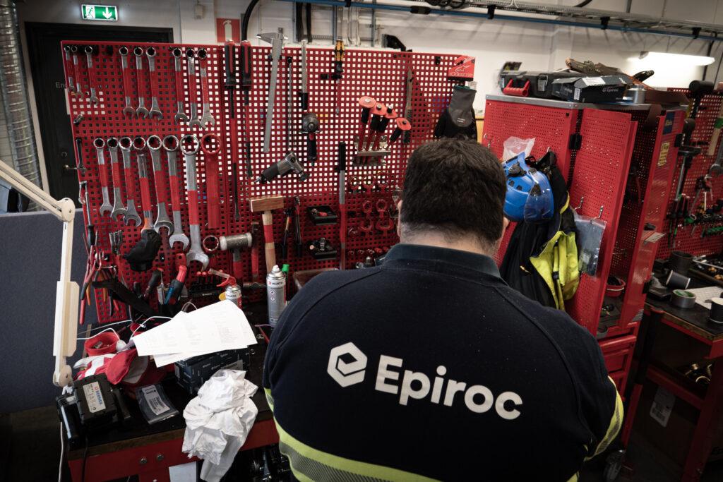 En mekaniker går igenom en bergborrmaskin i borrmaskinsverkstaden i Slagsta. Verktygen hänger prydligt framför honom.