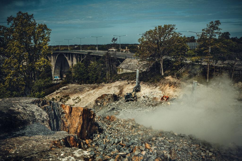 En borrigg ses vid sidan om Skurubron samtidigt som en sprängladdning fyras av i byggprojektet