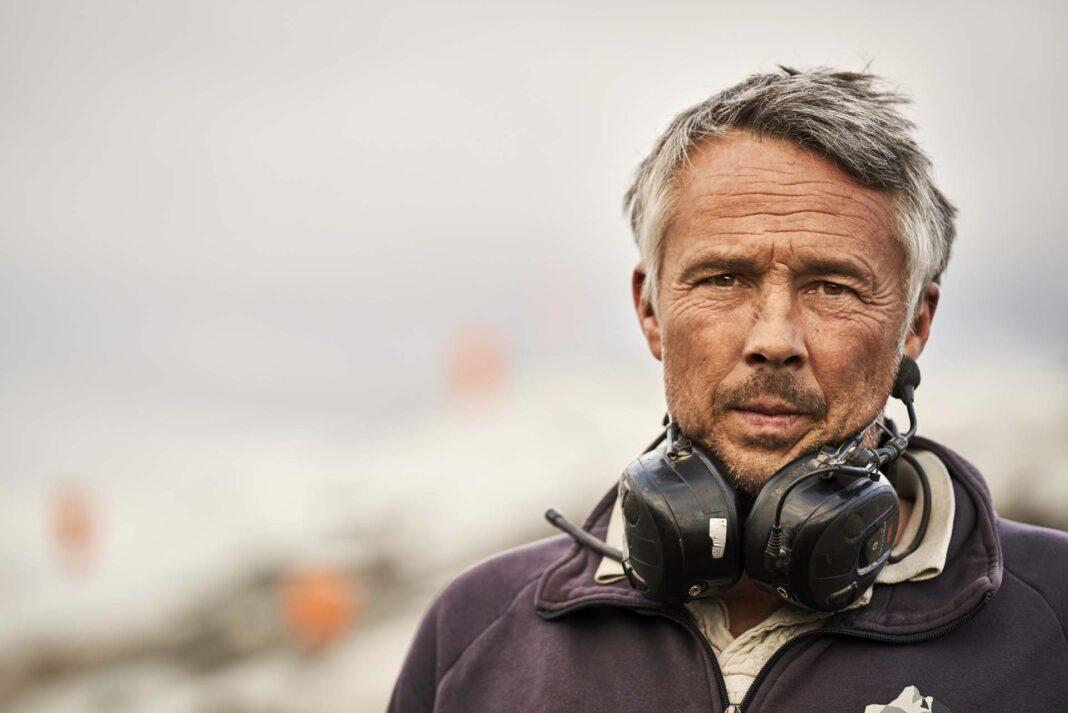 Stephen Jakobsen står på berget med sina hörselskydd runt nacken