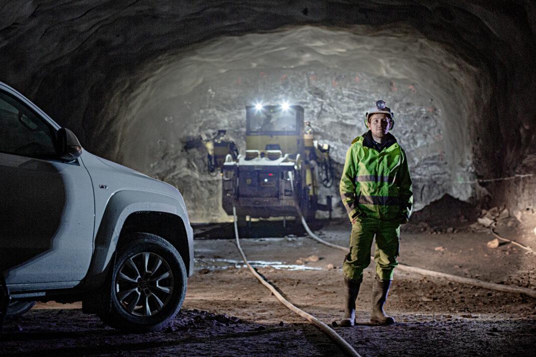 Thomas från Subterra står i tunneln förbifart stockholm framför en Epiroc Boomer
