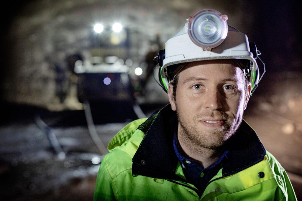 Tomáš Němeček står i tunneln med hjälm och pannlampa, i bakgrunden syns en borrigg från Epiroc