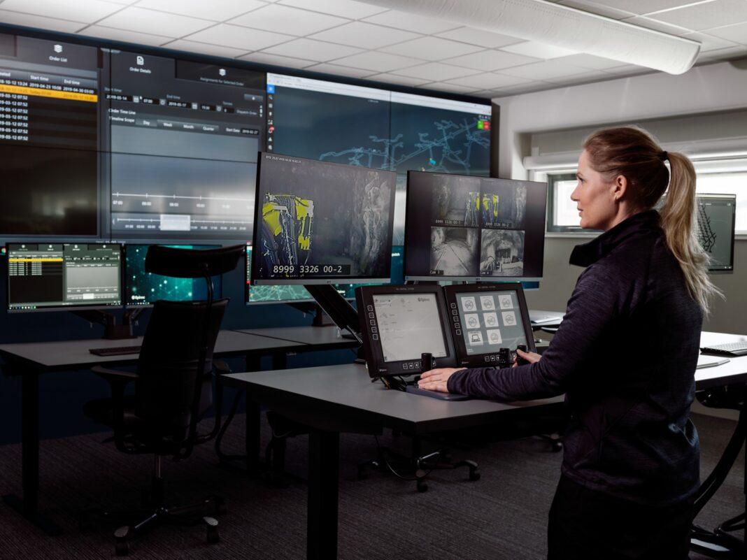 En kvinna står vid en kontrollpanel med många skärmar