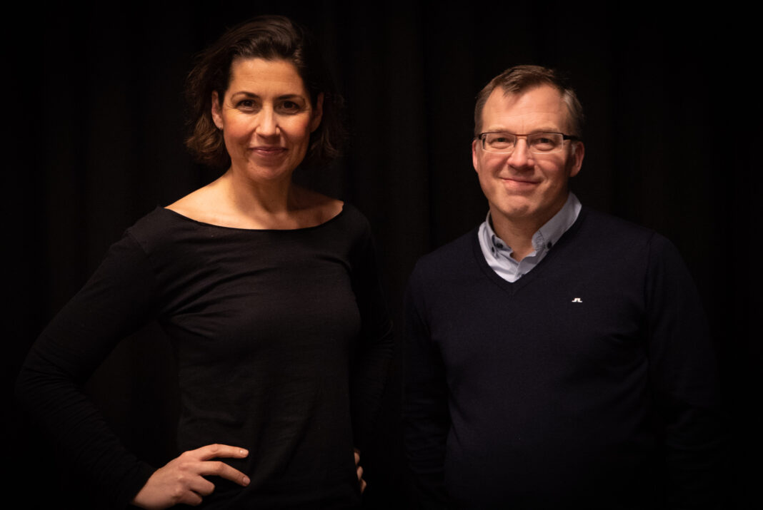 Två personer, Johanna Paues Darlington och Stefan Löfdahl står vända mot kameran med en mörk bakgrund.