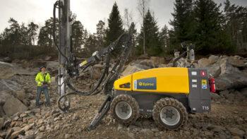 En gul Epiroc t15 borrvagn i profil vid en byggarbetsplats